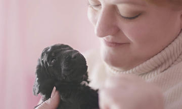 Woman looking lovingly at black puppy